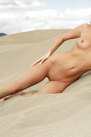 Hot blonde poses on a sandy beach