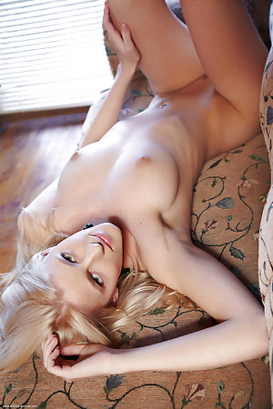 Blonde bombshell poses on the couch