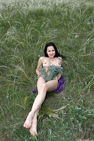 Arresting brunette naked in the wild with flowers