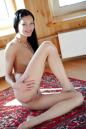 Raven haired woman is on the carpet, naked
