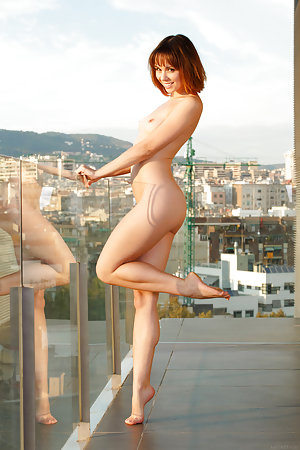 Playful minx is naked on the balcony