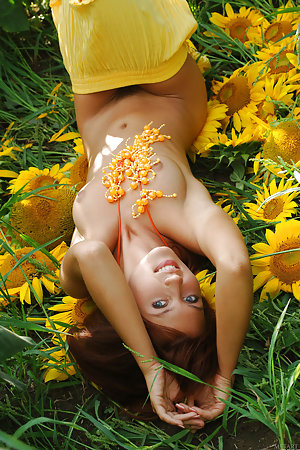 Redhead is in a field of sunflowers