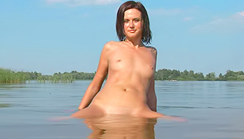 Skinny brunette bathes in a lake