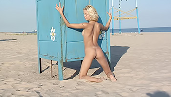 Cute blonde teen poses on the beach