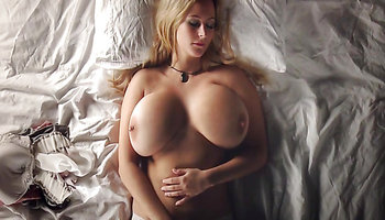 Blonde with giant boobs rubs her pussy hard in bed