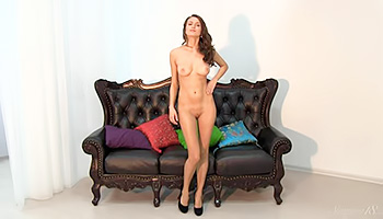 Slim brunette gets naked on her couch
